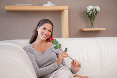 Smiling woman with a red rose sitting on the sofa Stock Image