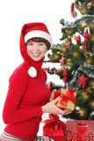 Smiling woman in red Santa hatunder Christmas tree Royalty Free Stock Photography