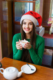 smiling woman in red Santas hat drinking tea in cafe Royalty Free Stock Image