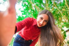 Smiling Woman in Red Shirt and Blue Jeans Taking Selfie Under Green Leaved Tree Stock Images