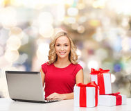 Smiling woman in red shirt with gifts and laptop Royalty Free Stock Image
