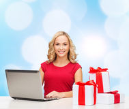 Smiling woman in red shirt with gifts and laptop. Christmas, holidays, technology, advertising and people concept - smiling woman in red blank shirt with gifts Royalty Free Stock Photography