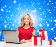 Smiling woman in red shirt with gifts and laptop. Christmas, holidays, technology, advertising and people concept - smiling woman in red blank shirt with gifts Stock Photo