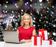Smiling woman in red shirt with gifts and laptop. Christmas, holidays, technology, advertising and people concept - smiling woman in red blank shirt with gifts Stock Image