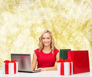 Smiling woman in red shirt with gifts and laptop Royalty Free Stock Photo