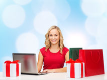Smiling woman in red shirt with gifts and laptop. Christmas, holidays, technology, advertising and people concept - smiling woman in red blank shirt with Stock Photography