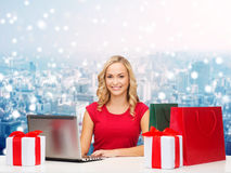 Smiling woman in red shirt with gifts and laptop Royalty Free Stock Photography