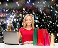 Smiling woman in red shirt with gifts and laptop. Christmas, holidays, technology, advertising and people concept - smiling woman in red blank shirt with Stock Photo