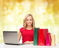 Smiling woman in red shirt with gifts and laptop. Christmas, holidays, technology, advertising and people concept - smiling woman in red blank shirt with Royalty Free Stock Photo