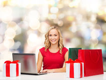 Smiling woman in red shirt with gifts and laptop Stock Photography