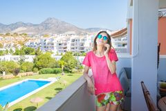 Smiling woman talking on mobile in the terrace next to pool Royalty Free Stock Photo