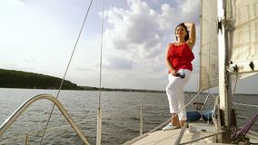 Smiling woman in red and white clothes relaxing on sailboat. Beautiful young woman in red and white summer clothes standing on deck of sailboat. Traveler stock video