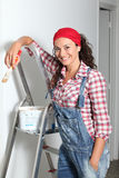 Smiling woman reforming house. Woman painting the walls of new home Stock Images