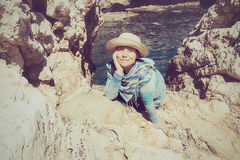 Smiling woman relaxes among rocks next to a calm sea Stock Images