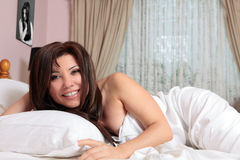Smiling woman relaxing in bed royalty free stock photography