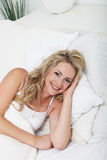 Smiling woman relaxing in bed Stock Images