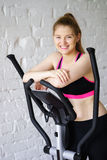 Smiling woman relaxing after cardio training. Loft interior Royalty Free Stock Photography
