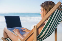 Smiling woman relaxing in deck chair on the beach using laptop. On a sunny day Royalty Free Stock Images