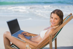 Smiling woman relaxing in deck chair on the beach using laptop Royalty Free Stock Photo