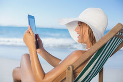 Smiling woman relaxing in deck chair on the beach using tablet Stock Photography