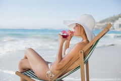 Smiling woman relaxing in deck chair with cocktail Stock Image