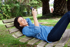 Smiling woman relaxing on hammock with mobile phone. Portrait of a smiling woman relaxing on hammock with mobile phone Royalty Free Stock Photography