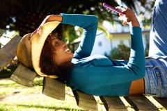 Smiling woman relaxing on hammock with mobile phone. Side portrait of a smiling woman relaxing on hammock with mobile phone Royalty Free Stock Photo