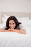 Smiling woman relaxing on her bed Royalty Free Stock Image