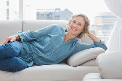 Smiling woman relaxing on her couch Royalty Free Stock Images