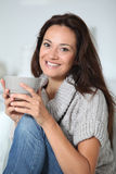 Smiling woman relaxing at home Stock Image