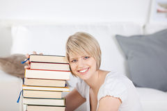 Smiling woman relaxing at home with her books Stock Images