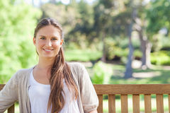 Smiling woman relaxing on a park bench Stock Photo