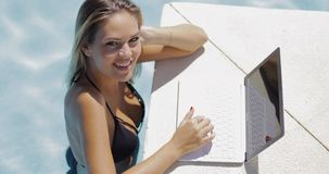 Smiling woman relaxing in pool with laptop Royalty Free Stock Photo