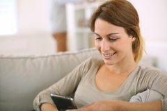 Smiling woman relaxing in sofa with smartphone in hands Royalty Free Stock Photos