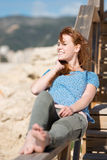Smiling woman relaxing in the sun. Lying barefoot in her jeans on a wooden railing overlooking a rocky seashore Stock Photo