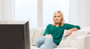 Smiling woman with remote watching tv at home Stock Photography