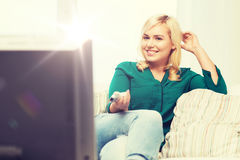 Smiling woman with remote watching tv at home Royalty Free Stock Photography