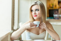 A woman in the restaurant is drinking coffee Stock Images