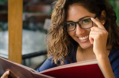 A smiling woman in a restaurant with the menu in hands royalty free stock images