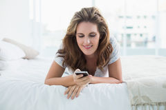 Smiling woman resting in bed text messaging Royalty Free Stock Photos