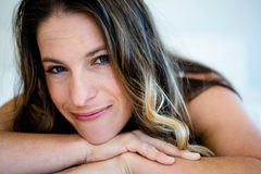smiling woman resting her head on her  hands Royalty Free Stock Image