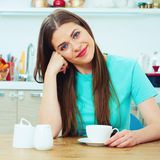 Smiling woman resting on kitchen Royalty Free Stock Photo