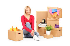 Smiling woman resting from moving into a new home. With many boxes around her Royalty Free Stock Images