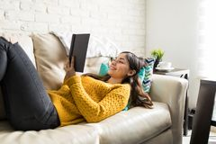 Smiling Woman Resting And Reading Stories. Young woman reading humorous novel while lying on sofa royalty free stock photography