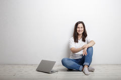 Smiling woman resting from work happy sitting by the wall on the. Smiling beautiful woman has a rest from work happy sitting by the wall on the floor next to Royalty Free Stock Photography