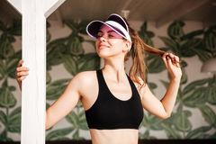 Smiling woman resting after workout on palm leaves pattern background Royalty Free Stock Photo