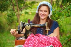 Smiling woman with retro hand sewing machine Stock Images