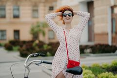Smiling woman rides bike in city, keeps hands behind on head, feels freedom, wears sunglasses and summer dress, stands near royalty free stock image