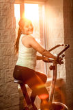 Smiling woman riding exercise bike at gym Stock Image