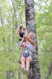 Smiling woman riding zip line in forest royalty free stock photo